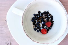 Some dry and fresh berries in a stack of dishes. Rustic composition with a dish and ladge vintage cup with some dry berry od black currants and two fresh red royalty free stock images