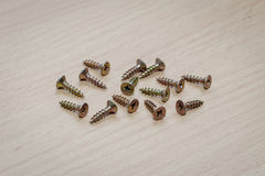 Some drywall Phillips screws on a wooden surface Royalty Free Stock Image