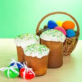 Some Easter cakes and eggs with bow. Some Easter cakes and eggs with a bow, a head of a basket, on a table on a green background Royalty Free Stock Photography
