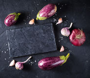 Some eggplants, garlic and red onion on a black board and backgr. Ound. Copy past. Top view Stock Photography