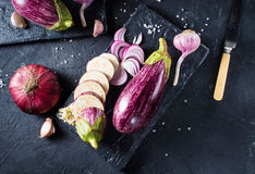 Some eggplants, garlic and red onion on a black board and backgr. Ound. Copy past. Top view Royalty Free Stock Photo