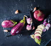 Some eggplants, garlic and red onion on a black board and backgr. Ound. Copy past. Top view Royalty Free Stock Photos