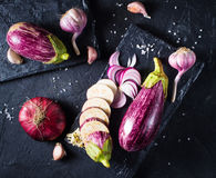 Some eggplants, garlic and red onion. On a black board and background Stock Photo
