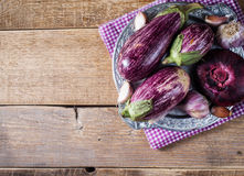 Some eggplants, garlic and red onion on a bowl. On wooden backgrpund stock image