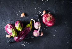 Some eggplants, garlic and red onion. On a black board and background Royalty Free Stock Image