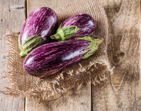 Some eggplants, garlic and red onion. On a wooden background stock photography
