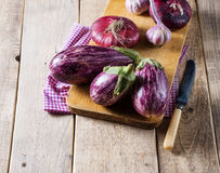 Some eggplants, garlic and red onion on a wooden board. Copy space Royalty Free Stock Image