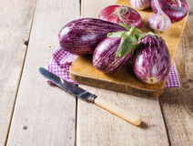 Some eggplants, garlic and red onion on a wooden board. Copy space stock image
