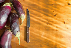 Some eggplants and knife on wooden surface. Food ingredients background. With place for text Royalty Free Stock Photos