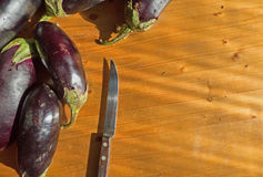 Some eggplants and knife on wooden surface. Food ingredients background. With place for text Stock Photography