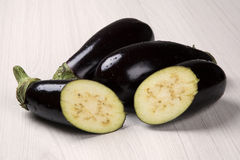 Some eggplants over a wooden surface. Fresh vegetable Stock Images