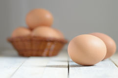 Some eggs in a basket on a white wooden table in a rustic kitchen. Empty copy space for editor's text Stock Photography