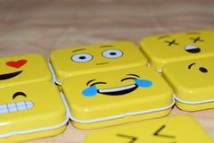 Emoji Metal Tins. Some emoji metal tins or smiley boxes, on a brown background stock images