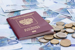 Some euro banknotes, coins and russian passport. Isolated on the table royalty free stock images