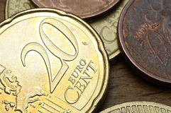 Some euro coins, one of twenty cent. On a wooden table Royalty Free Stock Photo