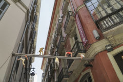 Some figurines between buildings in Malaga, Spain. Some figurines between buildings near Larios Street in Malaga, Spain Stock Photos