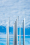 Some flagpoles and clouds in the blue sky.  stock images