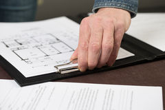 Some floorplans are clipped to a clipboard by an architect. Stock Images