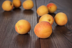 Some fresh apricots on brown table. Some fresh apricots over brown wooden background royalty free stock image