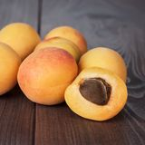 Some fresh apricots on brown table Royalty Free Stock Image
