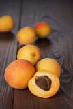 Some fresh apricots over wooden background. Some fresh apricots over brown wooden background stock photography