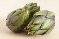 Some fresh artichokes. On a wooden board Stock Image