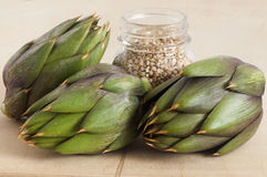 Some fresh artichokes. On a wooden board Stock Photos