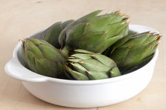 Some fresh artichokes. On a wooden board Royalty Free Stock Images