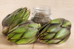 Some fresh artichokes. On a wooden board Royalty Free Stock Photo