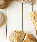 Some fresh bread on wooden table . frame composition. Rustic bread on white  wooden background Royalty Free Stock Photography