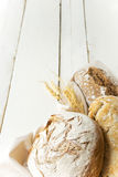 Some fresh bread on wooden table. Rustic bread on white  wooden background Royalty Free Stock Image
