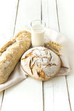 Some fresh breads on wooden table. Rustic bread on white  wooden background Royalty Free Stock Photo