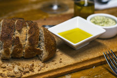 Some fresh brown bread on the wooden table. With oil and butter stock image