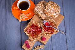Buns with jam and tea. Some fresh buns with raspberry jam and tea in orange cup royalty free stock images