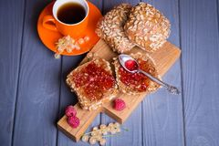 Buns with jam and tea. Some fresh buns with raspberry jam and tea in orange cup royalty free stock photo