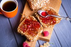 Buns with jam and tea. Some fresh buns with raspberry jam and tea in orange cup royalty free stock photos