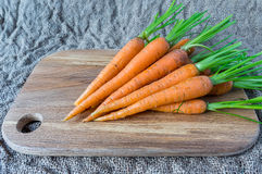 Some fresh carrots at the wooden plank.  Stock Photo