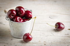 Some fresh cherries on wooden background. Some fresh cherries inside of small bucket on wooden background Royalty Free Stock Photos