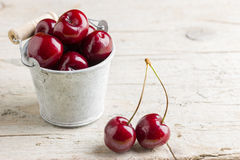 Some fresh cherries on wooden background. Some fresh cherries inside of small bucket and on wooden background Stock Photography