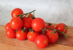 Some fresh cherry tomatoes. On a desk Stock Photos