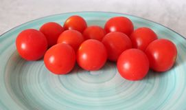 Some fresh cherry tomatoes. On a plate Royalty Free Stock Photos