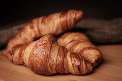 Some fresh croissants on a wooden surface Stock Photography