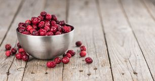 Some fresh Dried Cranberries on wooden background selective foc. Dried Cranberries on an old wooden table selective focus Royalty Free Stock Images