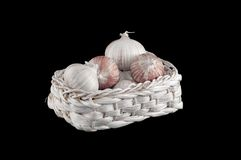 Some fresh garlic in athe basket. Some fresh garlic in the basket on black Royalty Free Stock Photography