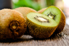 Some fresh Kiwi Fruits on an old wooden table. Some fresh Kiwi Fruits (selective focus) on an old wooden table, half of kiwi royalty free stock photos