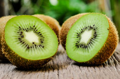 Some fresh Kiwi Fruits on an old wooden table. Some fresh Kiwi Fruits (selective focus) on an old wooden table, half of kiwi stock image