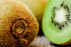 Some fresh Kiwi Fruits on an old wooden table. Some fresh Kiwi Fruits (selective focus) on an old wooden table, half of kiwi royalty free stock image
