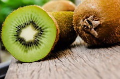 Some fresh Kiwi Fruits on an old wooden table. Some fresh Kiwi Fruits (selective focus) on an old wooden table, half of kiwi stock photo