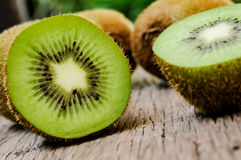 Some fresh Kiwi Fruits on an old wooden table. Some fresh Kiwi Fruits (selective focus) on an old wooden table, half of kiwi stock images