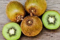 Some fresh Kiwi Fruits on an old wooden table. Some fresh Kiwi Fruits (selective focus) on an old wooden table, half of kiwi royalty free stock images